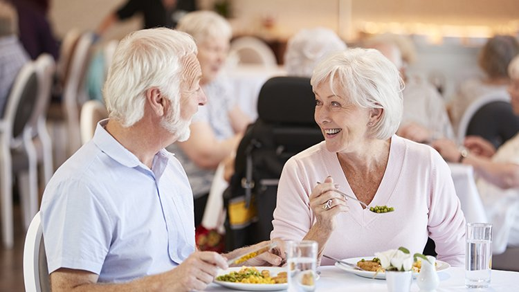 senior couple enjoying dining together in community