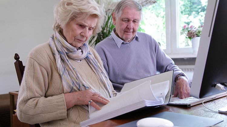 Senior couple reviewing critical documents at a table with a binder of documents and desktop computer.