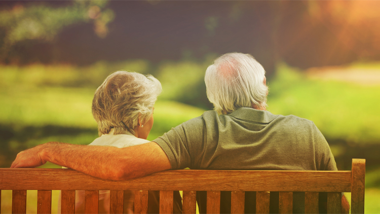 Senior couple sitting on a bench talking about a not-for-profit retirement community.