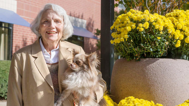 Older woman smiles with her pet dog outside her retirement community