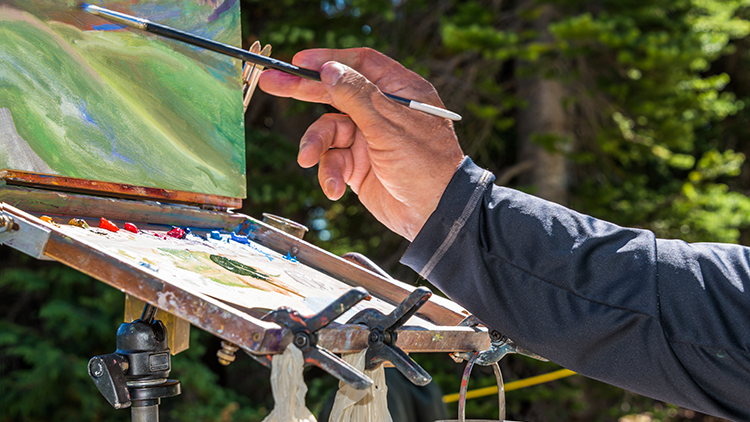 Senior man painting landscape image outdoors with oil paints