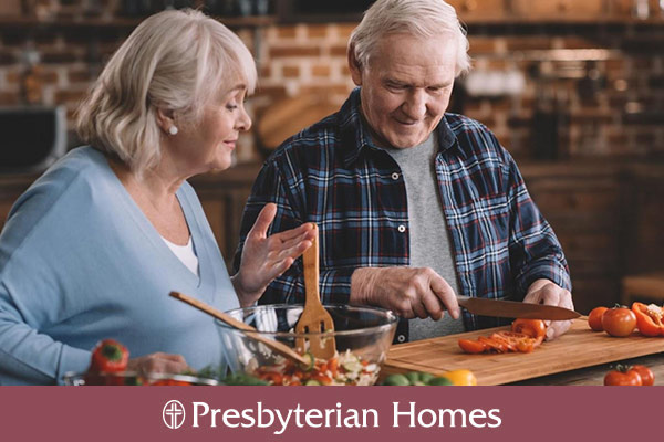 two older adults cooking a healthy meal together